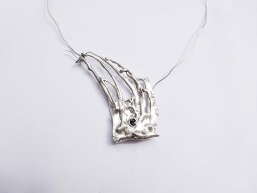 Un collier en argent avec un design qui ressemble à de l'herbe est exposé sur fond blanc.