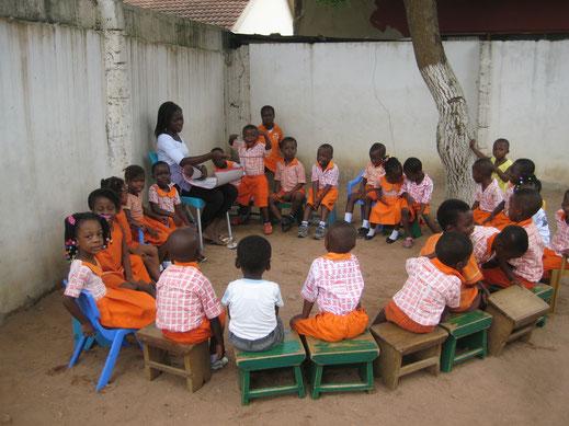 """Lernsituation im Stuhlkreis . Oft ist es unter dem Wellblechdach der sogenannten """"Klassenräume"""" so warm und stickig, dass die  ein oder andere Klasse sich nach draußen verzieht. Foto: Manuela Wiese"""