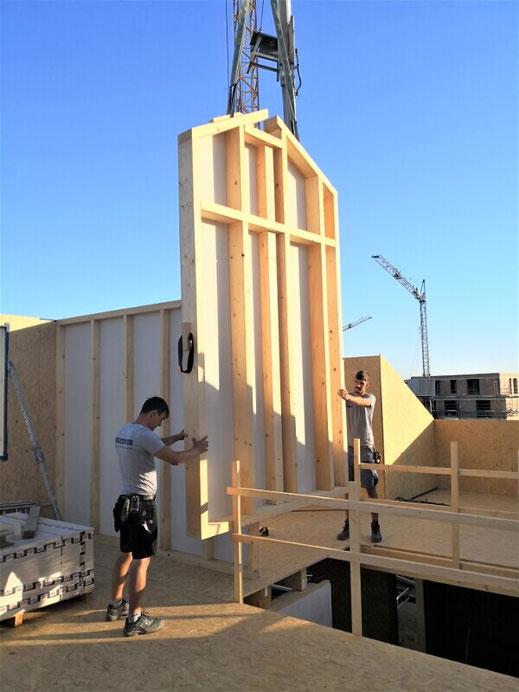 Montage eines Wandelements bei einem Ausbauhaus aus Holz