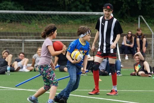 Kinder spielen Quidditch, daneben steht ein Schiedsrichter/Trainer