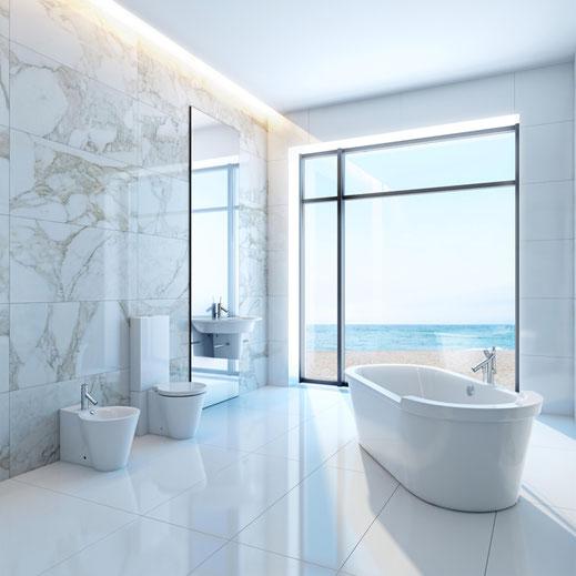 Gefliestes Badzimmer mit freistehender Badewanne und Blick auf Meer.