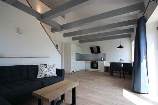 Wohnzimmer mit offener Balkenlage in der Ferienwohnung Schäfer's Loge