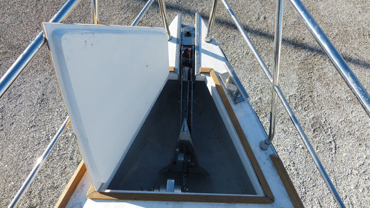 Deck of the semi displacement motor boat with a folding anchor platform