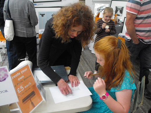 Lucy demonstrating dry point etching at Art In The Pen Skipton