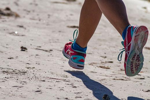 Ein paar Beine mit Laufschuhen mitten im Lauf als Symbol für Sport Coaching und in Bewegung kommen