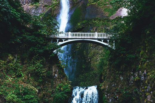 Eine Brücke als Verbindung in den Bergen vor einem Wasserfall als Symbol für das Finden gemeinsamer Lösungen