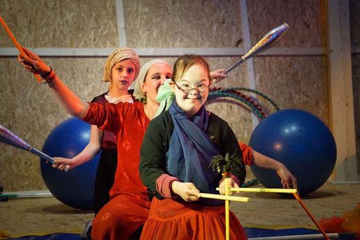 Eine Reihe von Zirkusartisten mit und ohne Behinderung. Vorne steht ein Mädchen mit Devilsticks, dahinter eine Gruppenleitung mit Devilsticks und dahinter ein Mädchen mit Keulen. Die Stimmung ist sehr gut.