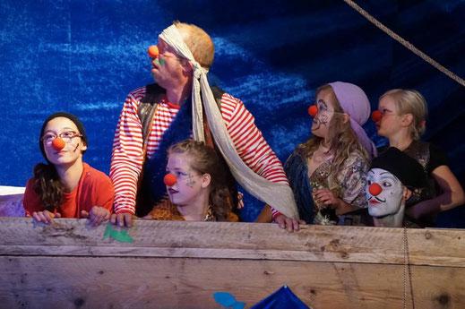Einige, als Clowns verkleidete Kinder und ein Clown stehen hinter einer Bootskulisse und schauen auf Etwas, was ich links vom Fotografen befindet.