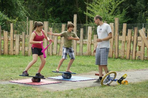 Ein Junge und ein Mädchen balancieren auf zwei Rola Bolas. Das Mädchen hält Pois in den Händen, der Junge macht Balance-Handbewegungen. Vor ihnen steht ein Mann, neben dem ein Einrad liegt.