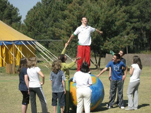 Ein junger Mann mit Downsyndrom steht auf einer Weltkugel und ist umringt von anderen jungen Menschen. Im Hintergrund ein Zirkuszelt.