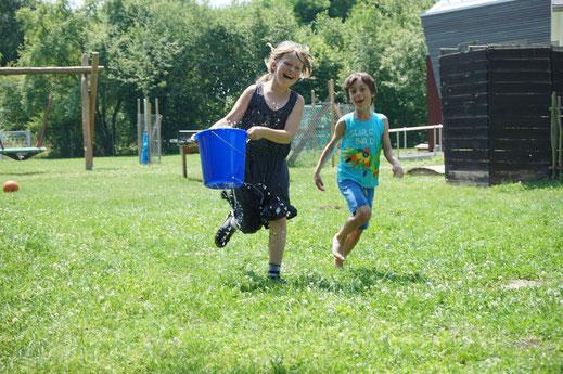 Ein Mädchen und ein Junge laufen lachend über eine Wiese. Das Mädchen hält einen Wassereimer in der Hand.