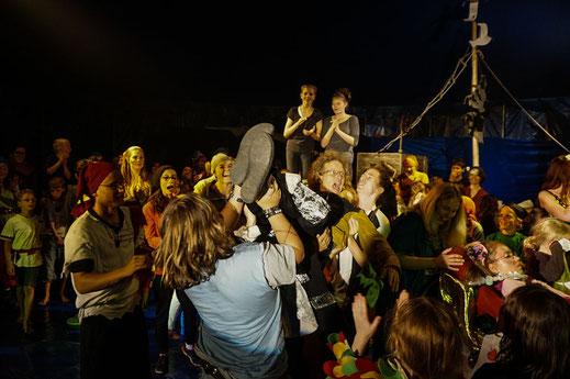 Viele Jugendliche freuen sich über eine gelungene Aufführung und lassen einen Mitarbeiter hochleben.