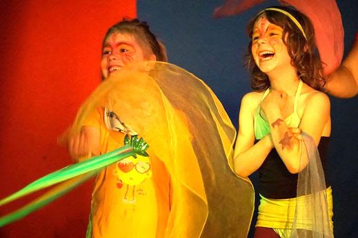 Zwei Mädchen in Kostüm lachen und spielen mit Tüchern.