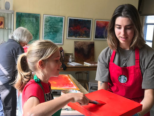 een jong, blond kine ne jonge vrouw met donkerblond haar zijn bezig een klein schilderdoek met oranje verf te bedekken.