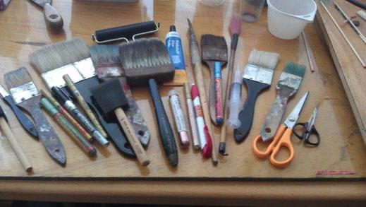 smalle en brede kwasten, een eekhoorharenkwast, een dasharen kwast, pennen, stiften, een linoroller en scharen, klaar om mee aan de slag te gaan