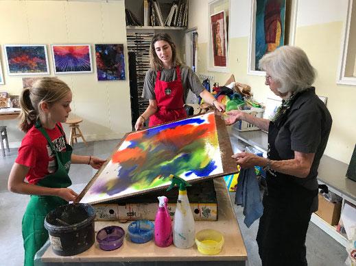 Oma en kleinkind workshop: een oma en twee kleinkinderen spelen samen met allerlei kleuren aquarelverf op een groot kleddernatpapier, de kleuren lopen in elkaar over, terwijl ze het bord heen en weer bewegen.