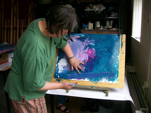 Een vrouw in een groen T-shirt schildert met haar handen met acryl verf in blauwen en wit-magenta-achtige mengingen een vogel in Atelier De Rode Draad