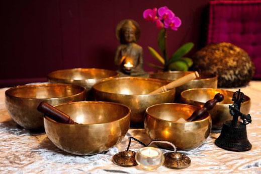 6 koperkleurige klankschalen, een Boeddha op de achtergrond en een orchidee. De schalen klaar om te worden bespeeld.