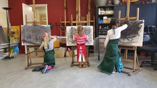 Drie kinderen staan voor hun ezel met tekenenboord. Ze tekenen met houtskool met twee handen op muziek om in beweging te komen