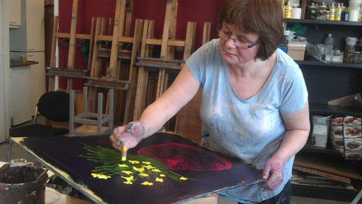 Cursist aan het werk in het atelier, De vrouw schildert met haar handen een pot narcissen. De gele bloemetjes lichten vrolijk op op een zwart-blauwe ondergrond