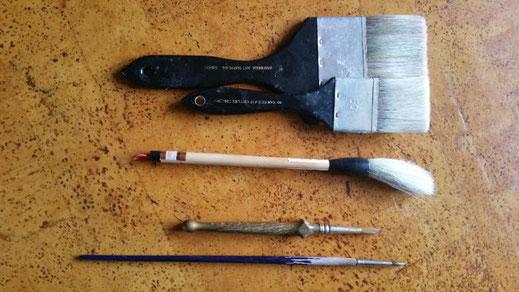 een brede en een smalle spalter, een Chinese kwast en twee marterharen penseeltjes op een kurken ondergrond