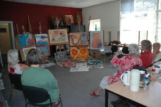 Cursisten zitten in een halve kring en kijken naar het schilderwerk op de ezels wat zij de afgelopen twee dagen hebben gemaakt