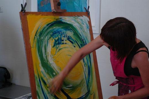 Een vrouw met donker haar maakt met een breed armgebaar een cirkel op een groot wit papier met de kleuren geel, groen en blauw.