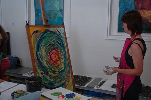 vrouw met zwarte kleding en roze schort en handen met verf erop, bekijkt haar schilderij. het een een spiralende cirekel met veel groen, donkerblwuw en een oranjerood hart. Ze neemt de tijd om te kijken hoe het nu verder moet.