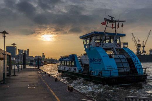 Sonnenaufgang an der Fischauktionshalle mit Blick gen Landungsbrücken und auf Hafenfähre HADAG