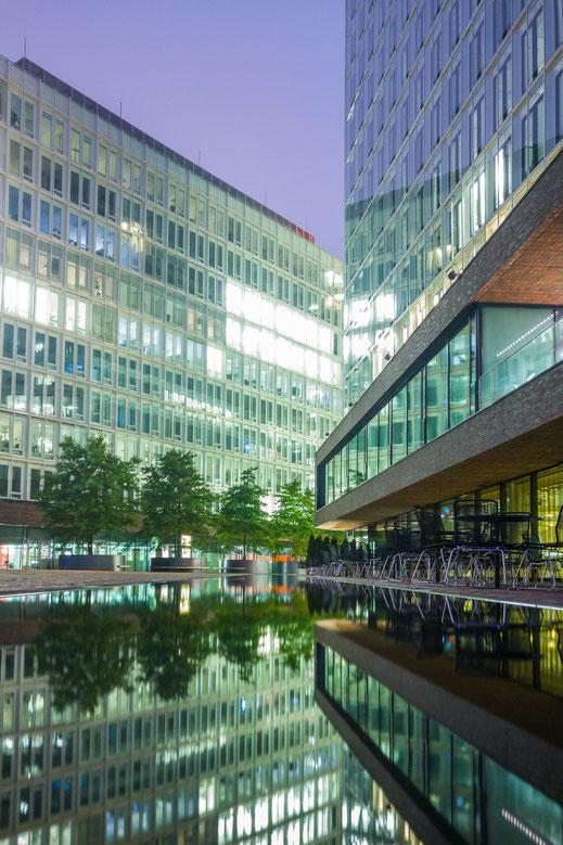 Wasserfläche mit Spiegelungen der umliegenden Gebäude