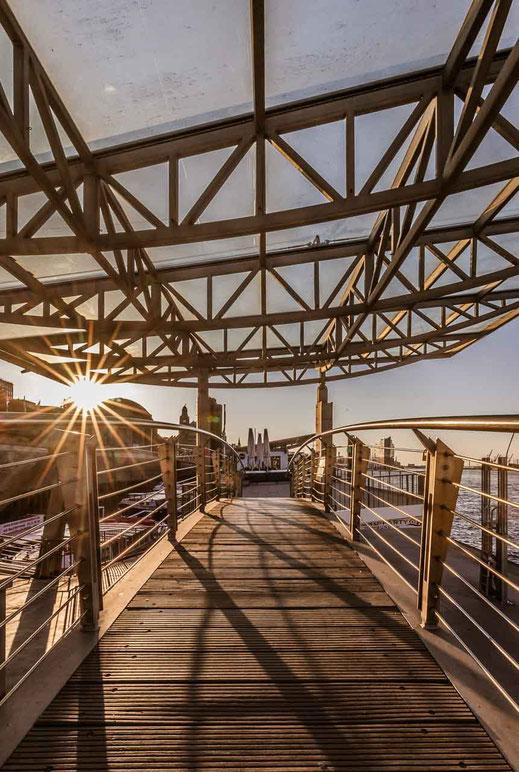 Linien durch Geländer an den Landungsbrücken mit Gegenlicht und Sonnenstern