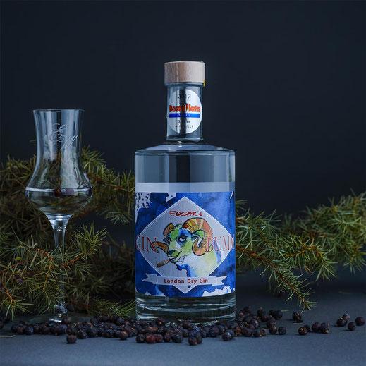 eine flasche london dry gin mit schnapsglas und wacholderbeeren
