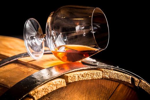 Ein Schnapsglas liegt auf Eichenholzfass