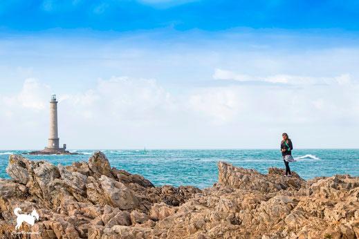 Eine junge Frau spaziert die Küste in Goury in der Normandie entlang