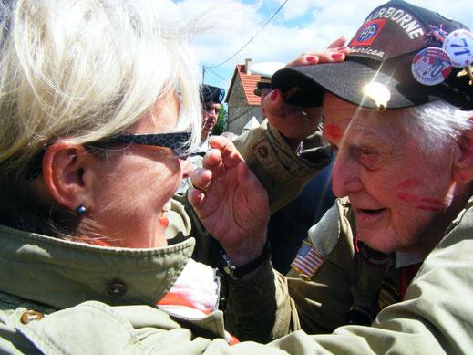 Ein US-Veteran wird während der D-Day-Feierlichkeiten in Carentan von einer jungen Französin geküsst.
