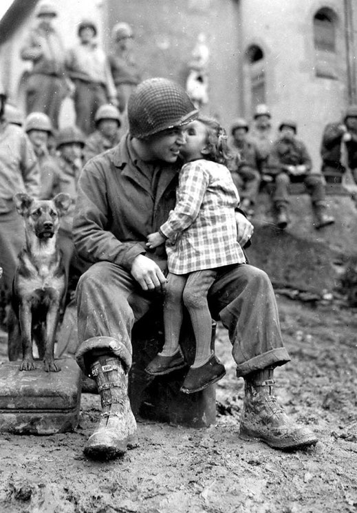 Ein Mädchen sitzt am D-Day auf dem Schoss eines US-Soldaten in der Normandie