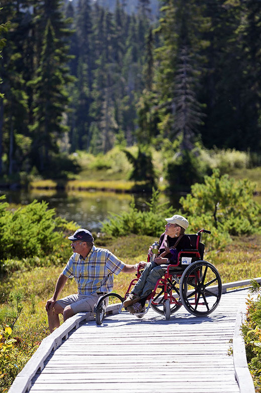 Man sitting on the boardwalk with woman in a wheel chair in Paradise Meadows.