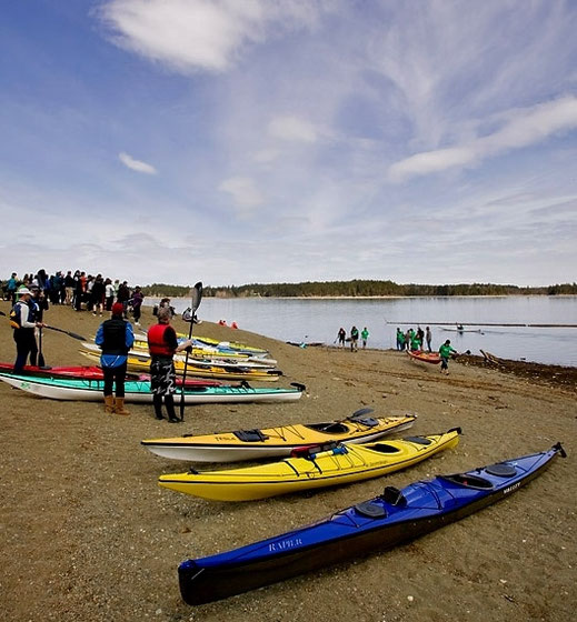 Kayaks and people on the beach at Comox Lake at the snow to surf relay.