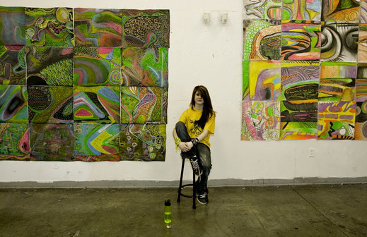 A young artist sitting with her artwork displayed behind her at a gallery in Courtenay.