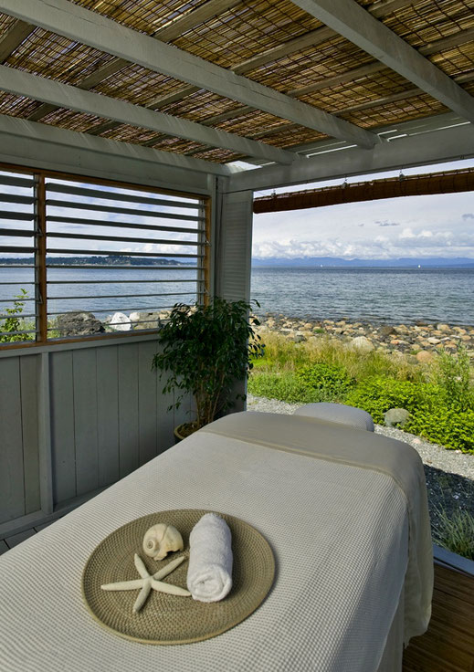 A message table and hut by the shore at a Comox Valley spa.
