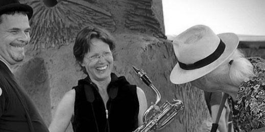 Anne Wiemann hat ihr Bariton Saxofon um, sie lacht in die Kamera. Vor ihr stehen Ulrich Wendt und Yogi Jockusch und lachen sie an.