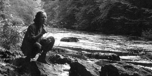 Frau sitzt am Ufer vom Fluss