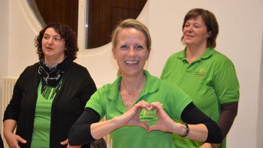 Lächelnde LandBiene umrahmt das Logo mit den Händen in Herzform.
