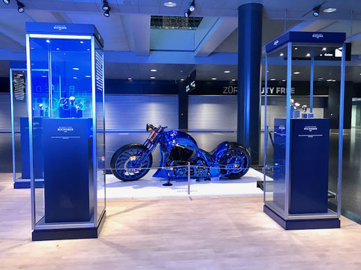 A blue Harley Davidson motorcycle on display between two showcases