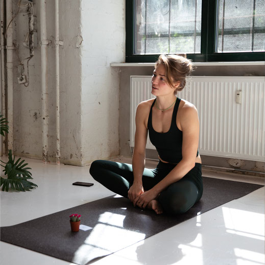 A female yoga teacher sitting on the dark recycled hejhej-mat and explaining the upcoming class.