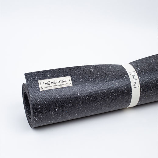 A close-up picture of the dark recycled hejhej-mat rolled up with a the hejhej-strap.