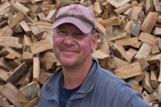 Bernd Lübbert vor Hintergrund aus Holz