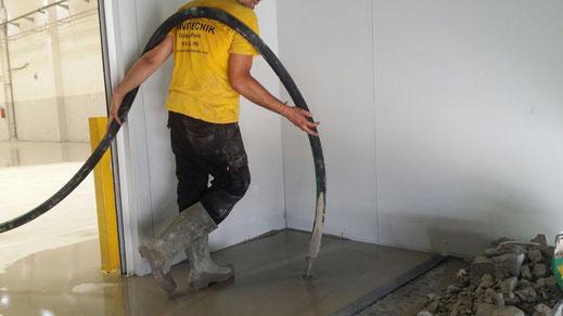 Vertido del mortero autonivelante cementoso con resistencias industriales en los pavimentos