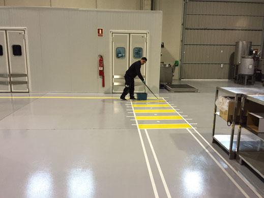 Suelos y pavimentos industriales de resinas continuos en Barcelona con un ejemplo de señalización