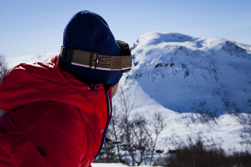 Man in red ski jacket looking at a mounatin